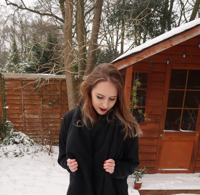 Girl in front of snowy shed in garden